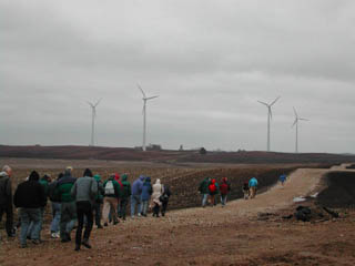 people walking across wind farm